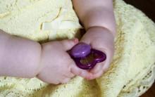 Vauva pitää tuttia käsissä.